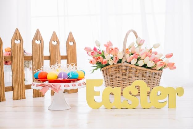 Oeufs de pâques colorés; panier de tulipes avec texte de pâques jaune sur le bureau en bois Photo gratuit