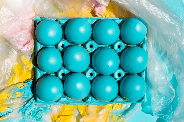 Oeufs de pâques colorés en rack sur cellophane peinte Photo gratuit