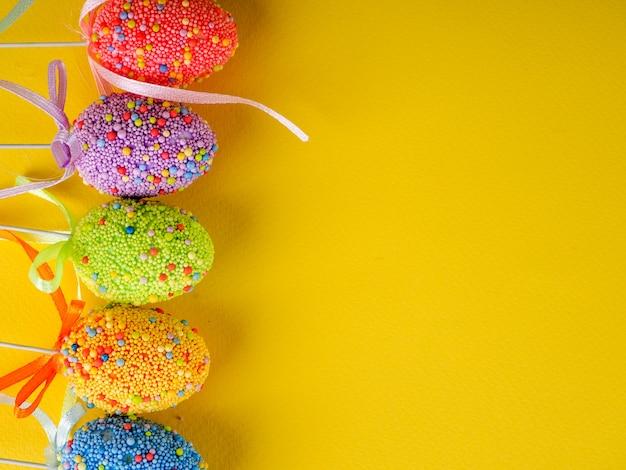 Oeufs De Pâques Colorés De Vacances De Pâques Sur Jaune Vif Photo Premium
