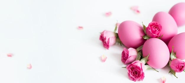 Oeufs de pâques décoratifs et roses roses oeufs de pâques roses sur fond clair. carte de vacances. Photo Premium