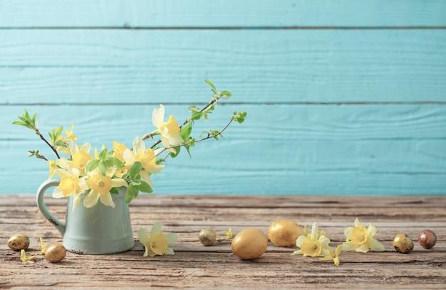 Oeufs De Pâques Dorés Et Fleurs Jaunes Sur Fond De Bois Photo Premium