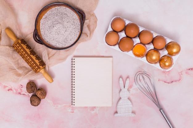 Œufs de pâques dorés sur un support avec un carnet, des ustensiles de cuisine et un lapin Photo gratuit