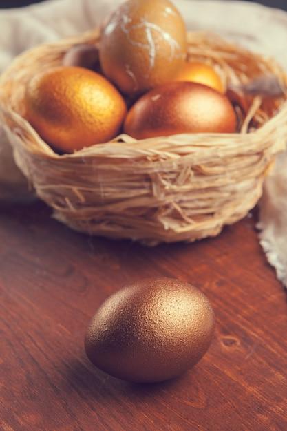 Oeufs de pâques dorés sur une table en bois Photo Premium