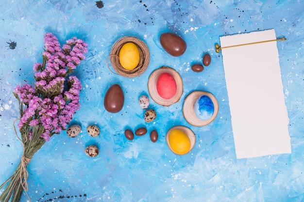 Oeufs de pâques avec du papier et des fleurs sur la table Photo gratuit