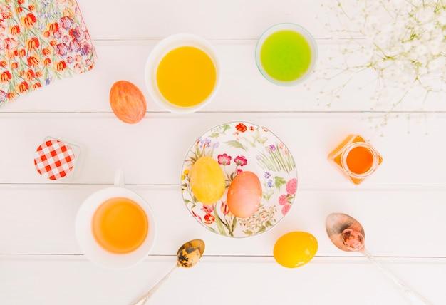 Œufs de pâques entre une assiette près de cuillères, une serviette de table et des coupelles Photo gratuit