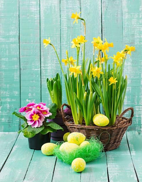 Oeufs De Pâques Et Fleurs Sur Un Mur En Bois Clair Photo Premium