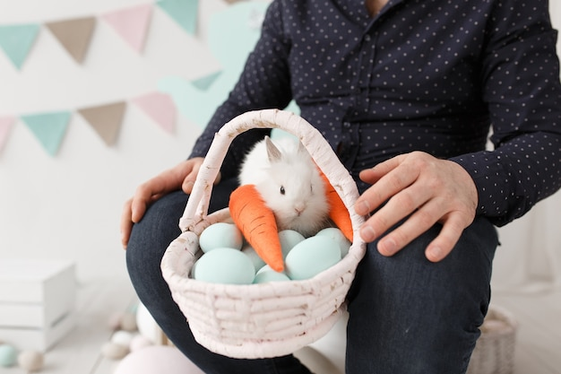 Oeufs de pâques et lapin dans le panier sur les tours de l'homme. Photo gratuit
