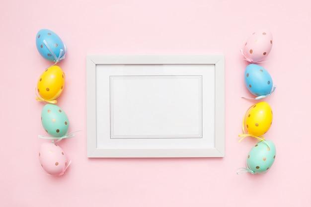 Oeufs De Pâques Multicolores Et Cadre Photo Blanc Sur Rose Photo Premium