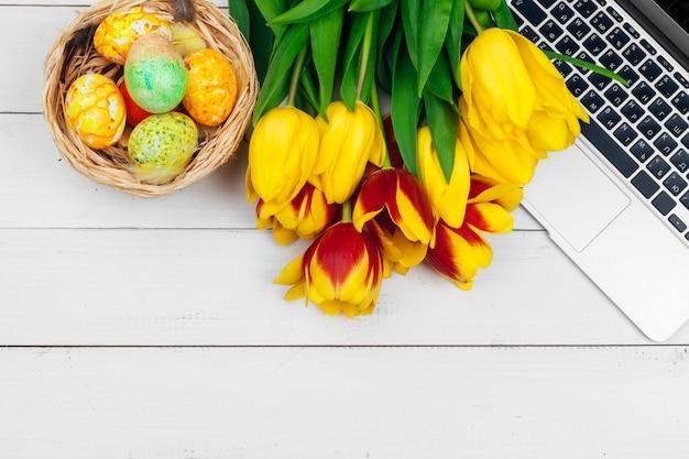 Oeufs de pâques, ordinateur portable et bouquet de tulipes. Photo Premium