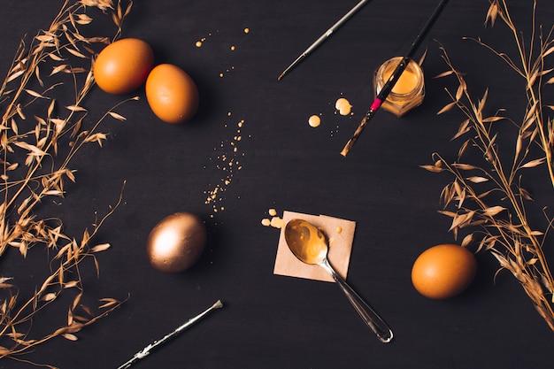 Œufs de pâques près de la cuillère sur le papier et le pinceau sur le colorant entre l'herbe sèche et les taches Photo gratuit