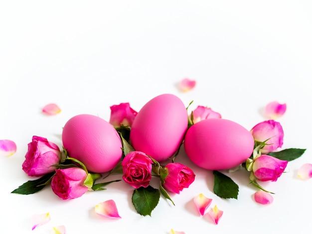Oeufs de pâques roses sur fond clair avec des roses roses. carte de vacances, espace copie. Photo Premium