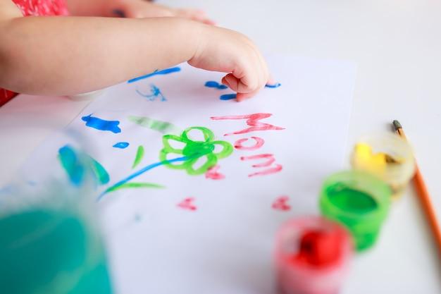 Oeufs De Pâques Sur Une Table En Bois Blanche. Des Fleurs Et Des Bonbons Tout Autour. Photo Premium