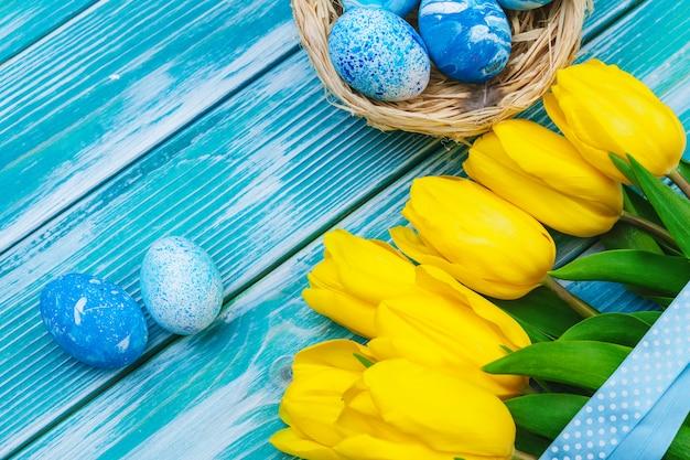 Oeufs de pâques et les tulipes. décoration de fête sur table en bois Photo Premium
