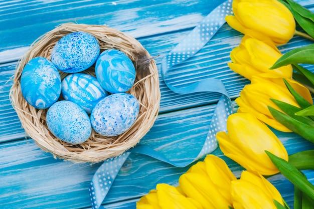 Oeufs de pâques avec des tulipes sur une planche de bois, concept de vacances de pâques. copyspace pour le texte Photo Premium