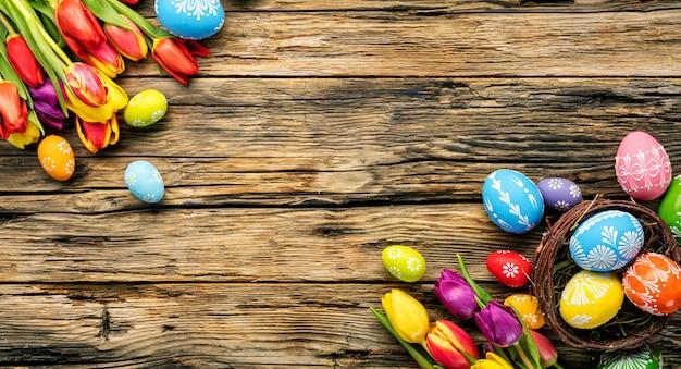 Oeufs De Pâques Et Tulipes Sur Planches De Bois Photo Premium