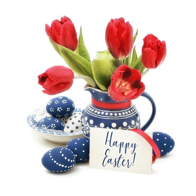 Oeufs de pâques et des tulipes rouges en céramique bleue sur blanc, texte Photo Premium