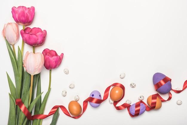 Oeufs de pâques avec des tulipes sur la table Photo gratuit
