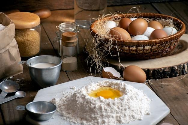Oeufs, pâte et farine sur une table en bois avec fond de splat pour un objet dans une boulangerie Photo Premium
