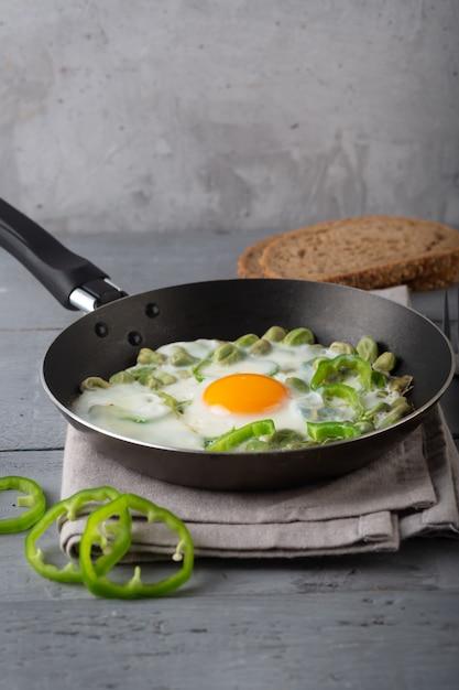 Œufs sur le plat avec du poivre frais sur gris Photo Premium