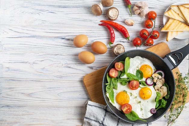 Œufs sur le plat avec des feuilles de tomates, champignons et épinards Photo Premium