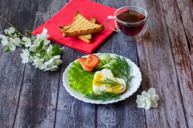 Œufs sur le plat avec des tranches de laitue, concombre et tomate sur fond en bois Photo Premium