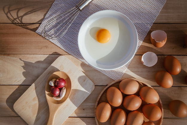 Les œufs pondent sur des plateaux en bois et ont des œufs cassés. Photo Premium