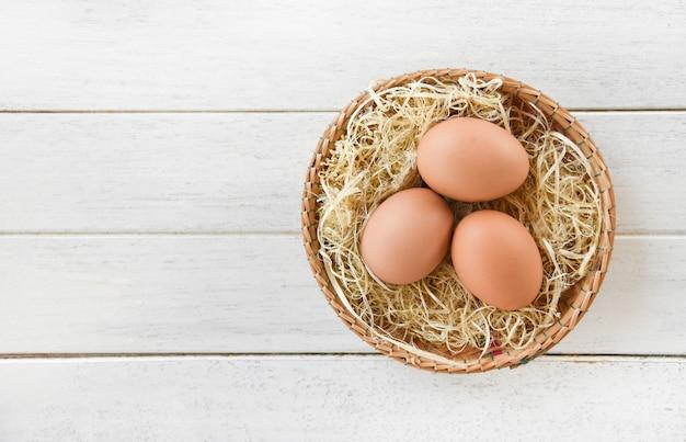 Œufs de poule au panier nid sur une table en bois Photo Premium