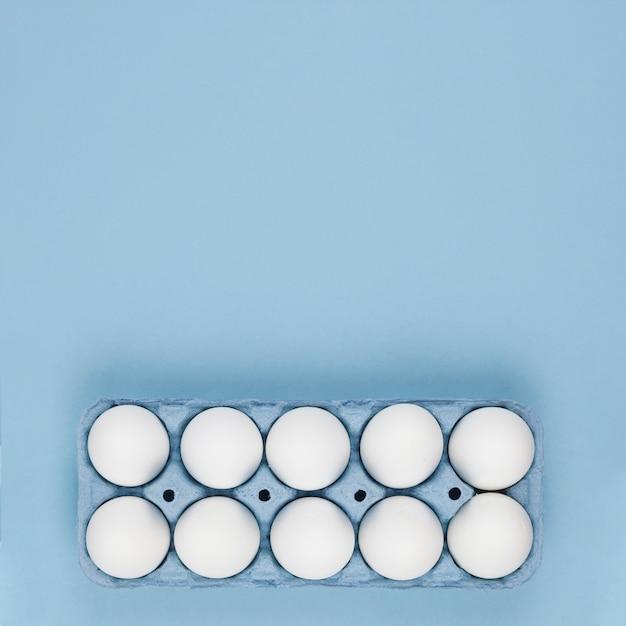 Œufs de poule blanche dans le support sur la table Photo gratuit