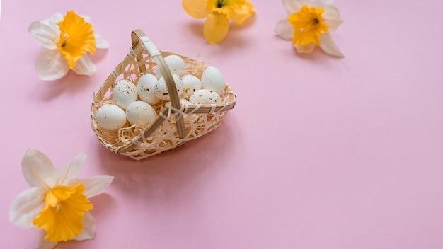 Œufs de poule blancs dans un panier avec des fleurs aux couleurs vives Photo gratuit