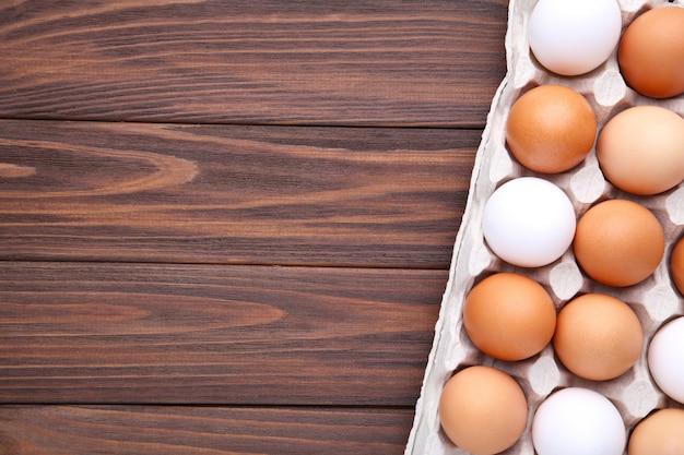 Œufs de poule dans des conteneurs sur fond en bois brun Photo Premium