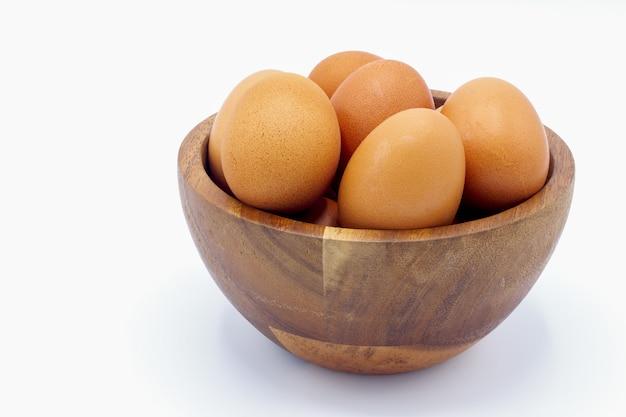 Œufs de poule frais dans un bol en bois sur un fond blanc Photo Premium