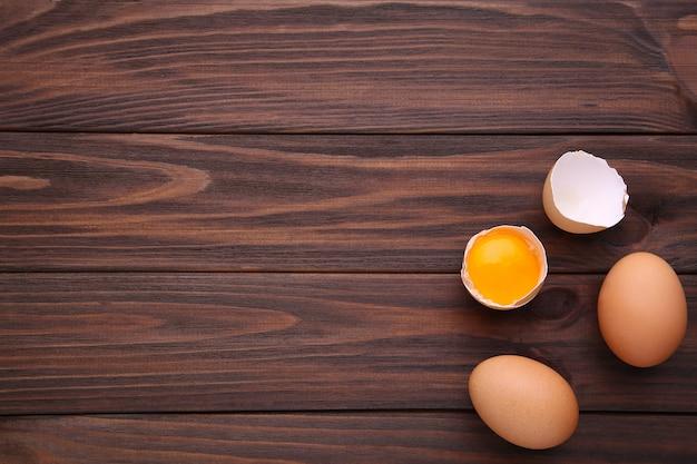 Œufs de poule et moitié avec du jaune sur un fond marron. Photo Premium