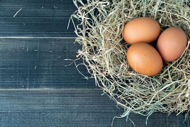 Œufs de poulet brun frais dans le nid de foin sur un fond en bois noir. Photo Premium