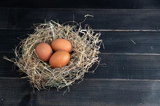 Œufs de poulet brun frais dans un nid de foin noir Photo Premium
