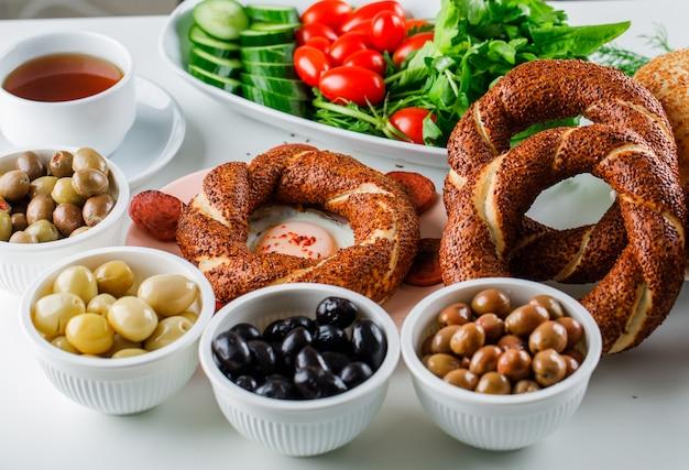 Oeufs Avec Saucisse En Plaque Avec Une Tasse De Thé, Bagel Turc, Salade Sur Une Surface Blanche Photo gratuit