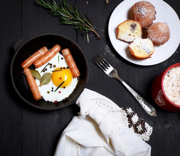 Oeufs avec des saucisses dans une poêle noire Photo Premium