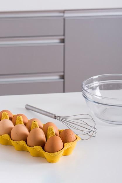Œufs de sourcils dans le carton jaune; fouet et bol en verre sur table blanche Photo gratuit