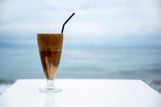 ? Offee Boire Avec De La Mousse Et De La Paille Sur Un Tableau Blanc Avec Mer Photo Premium