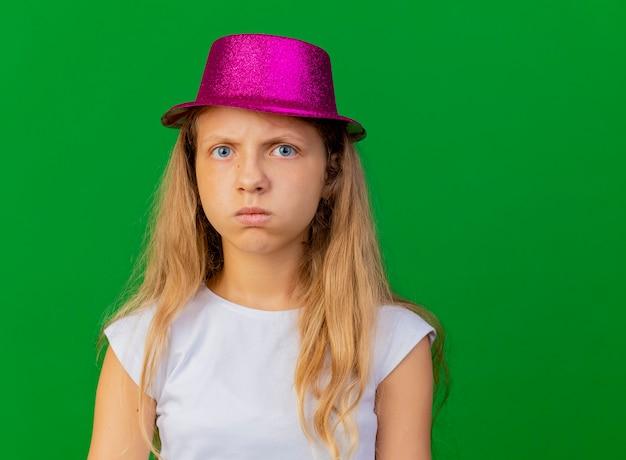 Offensé Jolie Petite Fille Au Chapeau De Vacances Avec Un Visage Sérieux Photo gratuit