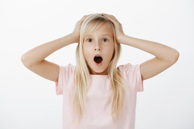 Oh Non, J'ai Des Ennuis. Confus Nerveux Jeune Fille Adorable Aux Cheveux Blonds, La Mâchoire Tombante Et Haletant, Se Tenant La Main Sur La Tête, Se Sentant Anxieux Après Avoir Brisé La Fenêtre, Ne Sachant Pas Quoi Faire Photo gratuit