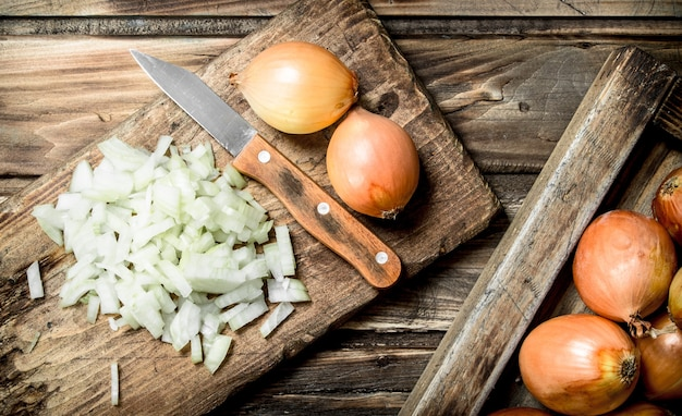 Oignon Finement Haché Sur Une Planche à Découper Avec Un Couteau. Sur Bois Photo Premium