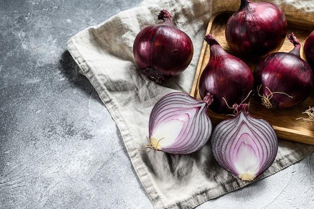 Oignon rouge dans un bol en bois, oignons coupés en deux. légumes écologiques de la ferme. fond gris. vue de dessus Photo Premium