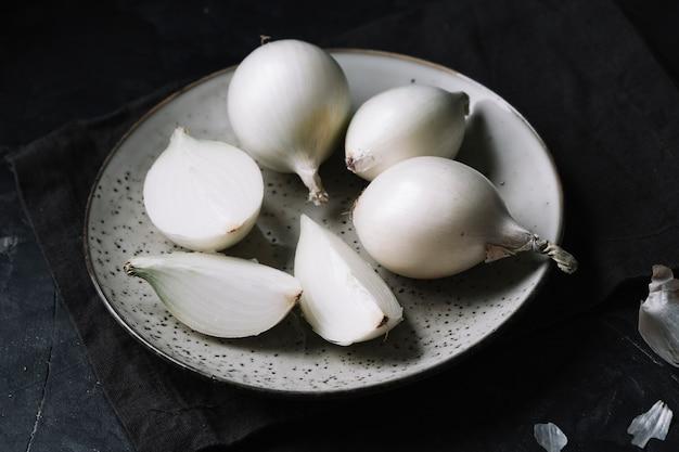 Oignons blancs sur une assiette avec un fond noir Photo gratuit