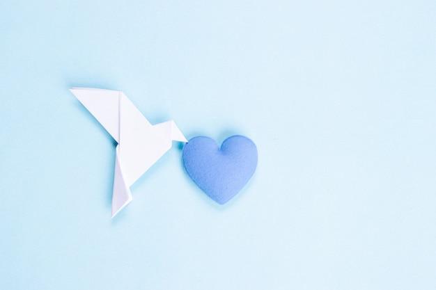 Oiseau Blanc En Papier Portant Un Coeur Bleu. Journée Internationale De La Paix. Photo Premium