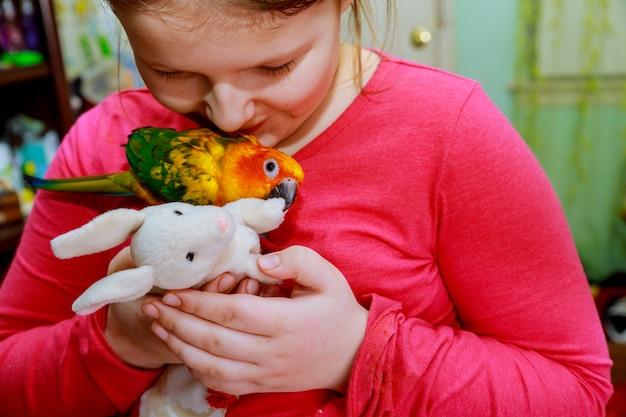 Oiseau perroquet sur la main de la jeune fille concept environnement humain et nature souriant jouant avec son animal de compagnie oiseau. Photo Premium