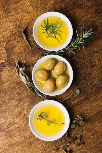 Olive et huile avec vue de dessus de bols disposés romarin Photo gratuit
