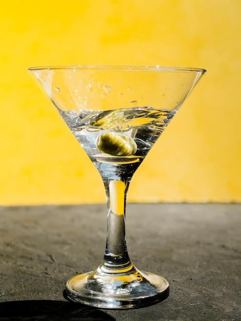 Olive verte éclaboussant en martini Photo gratuit