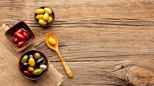 Olives dans des bols et une cuillère en bois avec espace de copie Photo gratuit