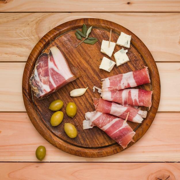 Olives; gousse d'ail; tranche de fromage et bacon sur un plateau en bois au-dessus du bureau Photo gratuit