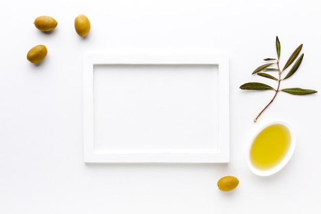Olives jaunes et soucoupe à l'huile avec maquette du cadre Photo gratuit